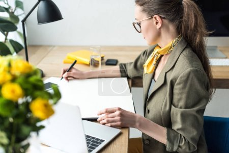 high angle view of stylish buisnesswoman in eyeglasses taking notes while sitting at workplace