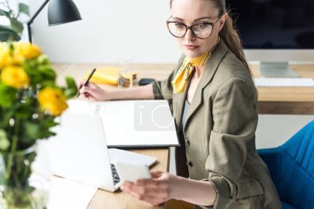 Foto de Vista de ángulo alto de hermosa empresaria en gafas con ordenador portátil y smartphone en oficina - Imagen libre de derechos