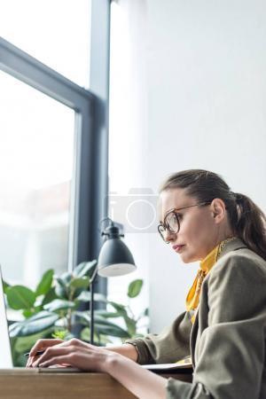 Photo pour Axé sur le milieu femme d'affaires âgé à l'aide d'ordinateur portable et bureau - image libre de droit