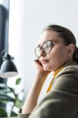 beautiful pensive businesswoman in eyeglasses looking away at workplace