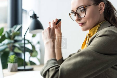 Photo pour Vue latérale de la belle buisnesswoman en lunettes assis au milieu de travail - image libre de droit