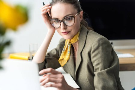 attractive mid adult businesswoman in eyeglasses sitting at workplace