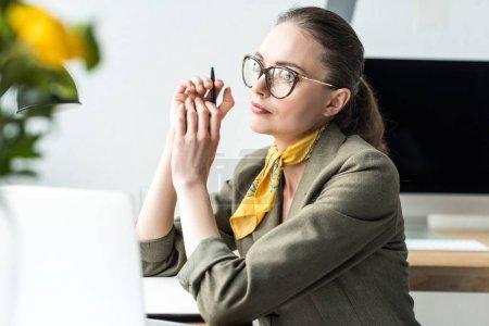 Photo pour Belle femme d'affaires pensif assis au milieu de travail et à la recherche de suite au bureau - image libre de droit