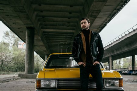 handsome stylish young man in leather jacket standing with hands in pockets near yellow retro automobile