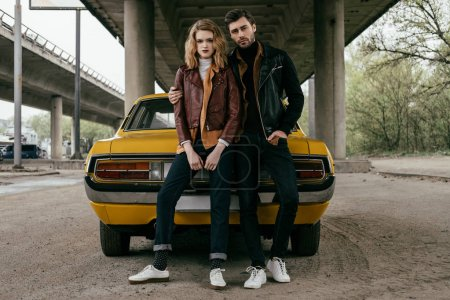 full length view of young couple in leather jackets sitting on yellow old-fashioned car and looking at camera