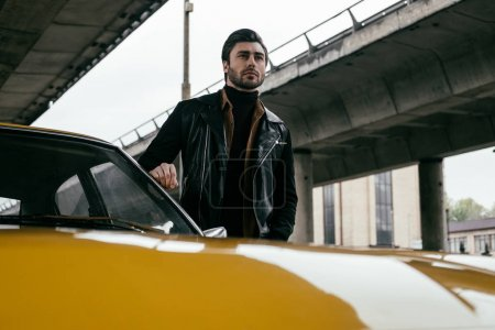 handsome stylish young man in leather jacket standing near yellow classic car and looking away