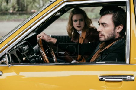 young woman looking at handsome stylish boyfriend driving yellow car