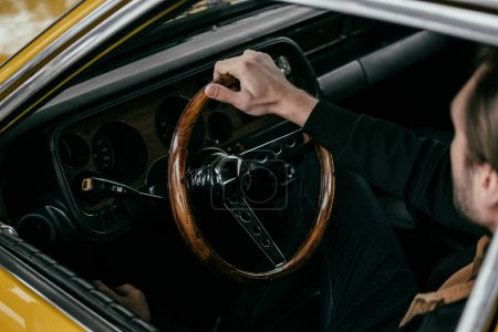high angle view of man holding steering wheel of old-fashioned automobile