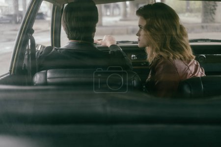 back view of stylish girl looking at handsome boyfriend driving car
