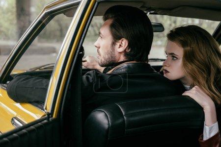Photo pour Vue arrière du beau jeune couple élégant assis dans une voiture rétro - image libre de droit