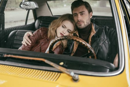 stylish thoughtful young couple in leather jackets sitting together in old-fashioned car