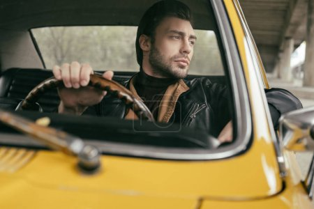 Photo for Pensive handsome stylish man sitting in vintage car and looking away - Royalty Free Image