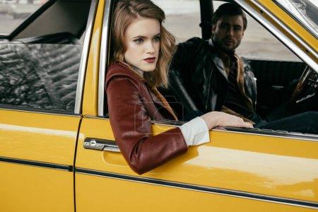 Foto de Atractivo joven mirando a bella novia sentado en coche clásico amarillo - Imagen libre de derechos