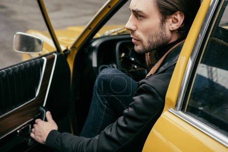side view of handsome stylish man opening door and looking away while sitting in retro car
