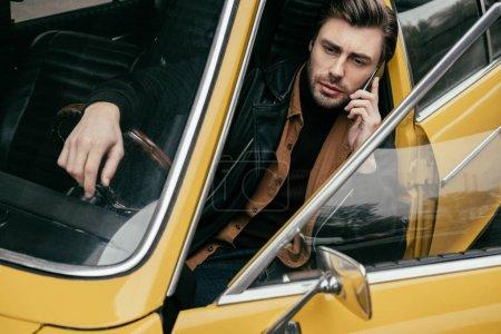 bel homme élégant parler de smartphone tout en étant assis dans une voiture classique jaune