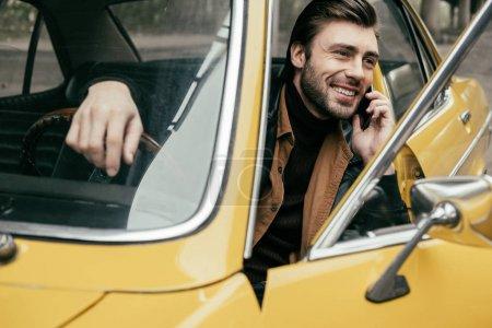 beau jeune homme souriant talking par smartphone tout en étant assis dans une voiture vintage jaune