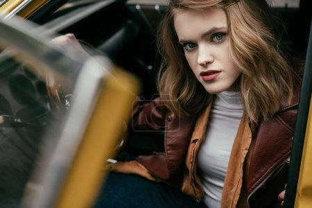 beautiful stylish young woman sitting in old-fashioned car and looking at camera