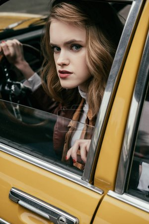 close-up view of girl looking at camera while sitting in classic car