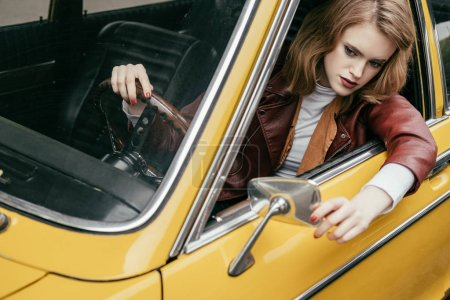 high angle view of beautiful stylish young woman in leather jacket sitting in yellow vintage car