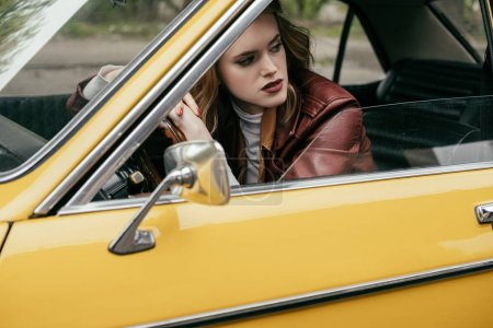 attractive girl leaning at steering wheel and looking away while sitting in yellow vintage car