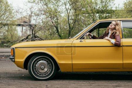 Foto de Vista lateral de hermosa mujer joven mirando a cámara mientras está sentado en el coche clásico amarillo - Imagen libre de derechos