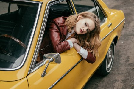 high angle view of beautiful stylish girl looking at camera through window of yellow classic car