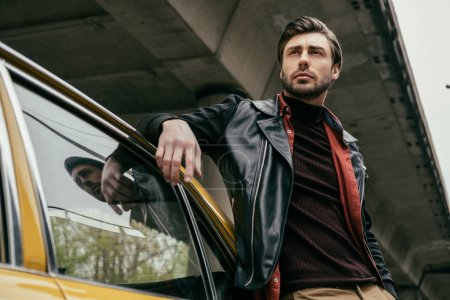 low angle view of handsome man leaning at car and looking away