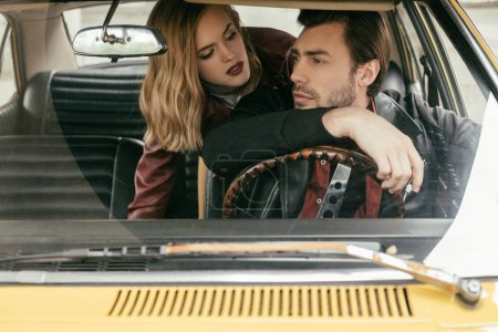 seductive girl looking at handsome boyfriend driving old-fashioned automobile