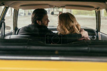 Photo pour Vue arrière du jeune couple embrassant et en regardant l'autre dans une voiture rétro - image libre de droit