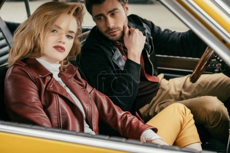 stylish young couple in leather jackets sitting together in vintage car