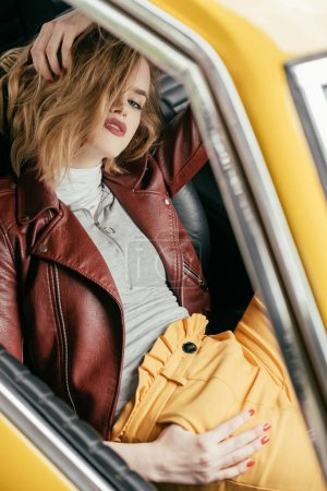 high angle view of stylish girl in leather jacket sitting in vintage car and looking at camera