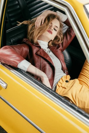 high angle view of stylish young woman sitting in vintage car and looking at camera
