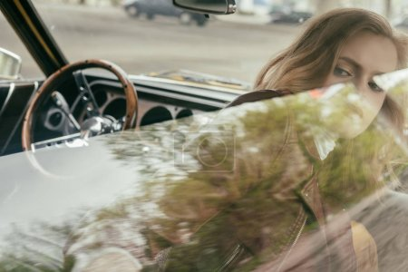 view through the window of beautiful girl sitting in vintage car