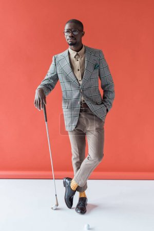fashionable african american golfer with golf club and ball, on red