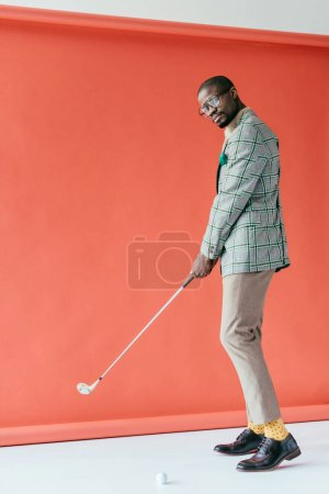 fashionable african american man playing golf, on red