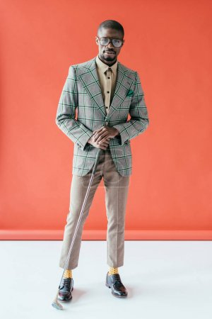 young stylish african american golfer with golf club, on red