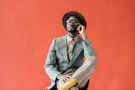 Foto de Hombre afroamericano en anteojos vintage hablar de smartphone, aislado en rojo - Imagen libre de derechos
