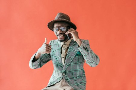 fashionable african american man with thumb up talking on smartphone, isolated on red