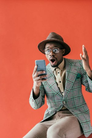 excited fashionable african american man using smartphone, isolated on red