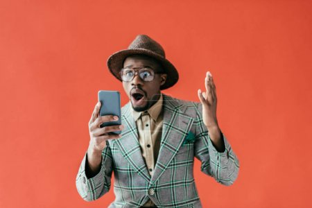 shocked african american man using smartphone, isolated on red