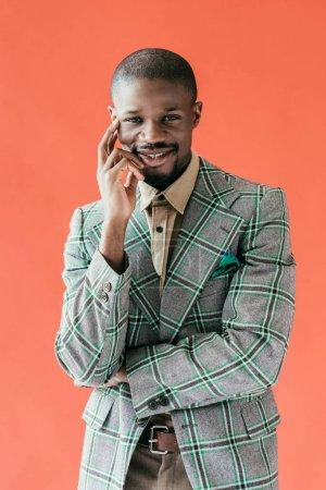 Photo pour Bel homme afro-américain souriante posant dans veste vintage, isolé sur le rouge - image libre de droit