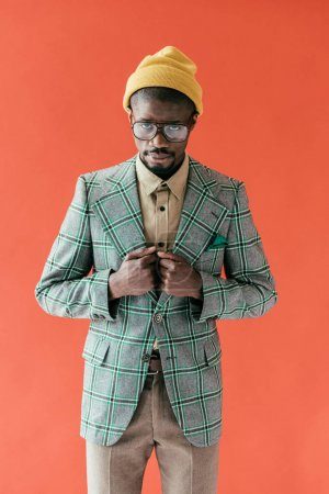 handsome african american man in vintage glasses and jacket, isolated on red