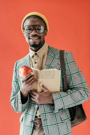african american student in retro jacket with book and apple, isolated on red