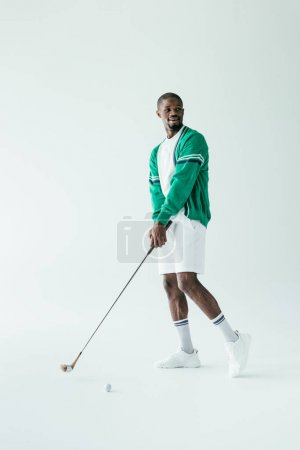 african american golfer in vintage sportswear playing game, isolated on white