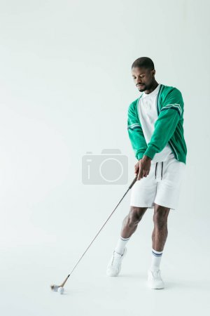 fashionable african american man playing golf, isolated on white