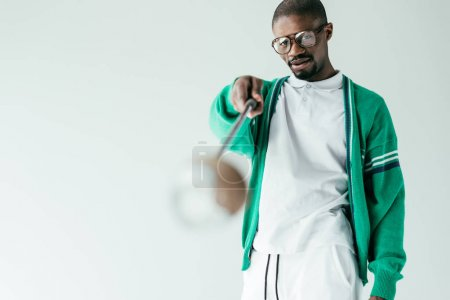selective focus of african american man in retro green sportswear with golf club, isolated on white