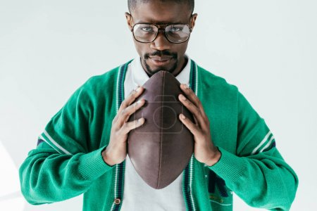 handsome african american man holding rugby ball, isolated on white