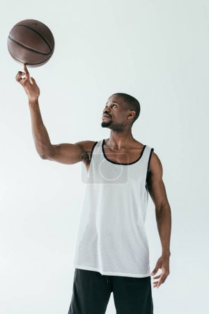 athletic african american basketball player spinning ball on finger, isolated on white