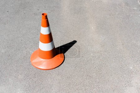 Photo for Orange and white traffic cone on asphalt road - Royalty Free Image