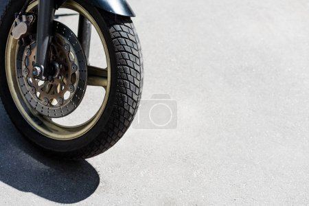 Front wheel with black tire of motorcycle on street